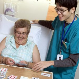 Youth playing cards with elderly patient