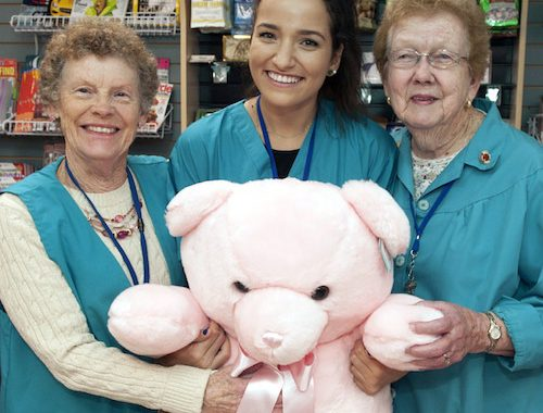 three women holding a big teddy bear