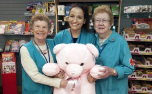 three smiling women holding large teddy bear