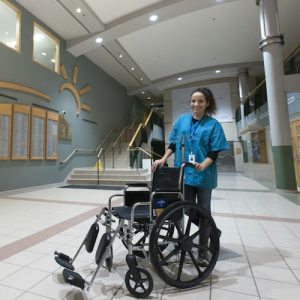woman standing with empty wheelchair